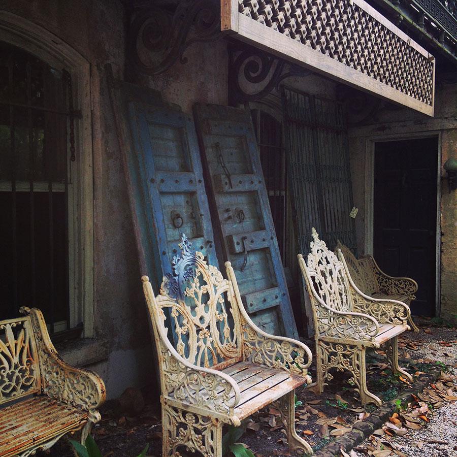 おしゃれな建物の一回に雑然と置かれた白い椅子とブルーの扉。